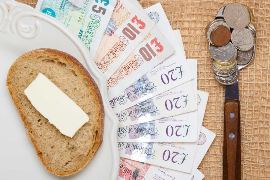 Bread and butter on a plate on top of a pile of money to show budgets are like diets