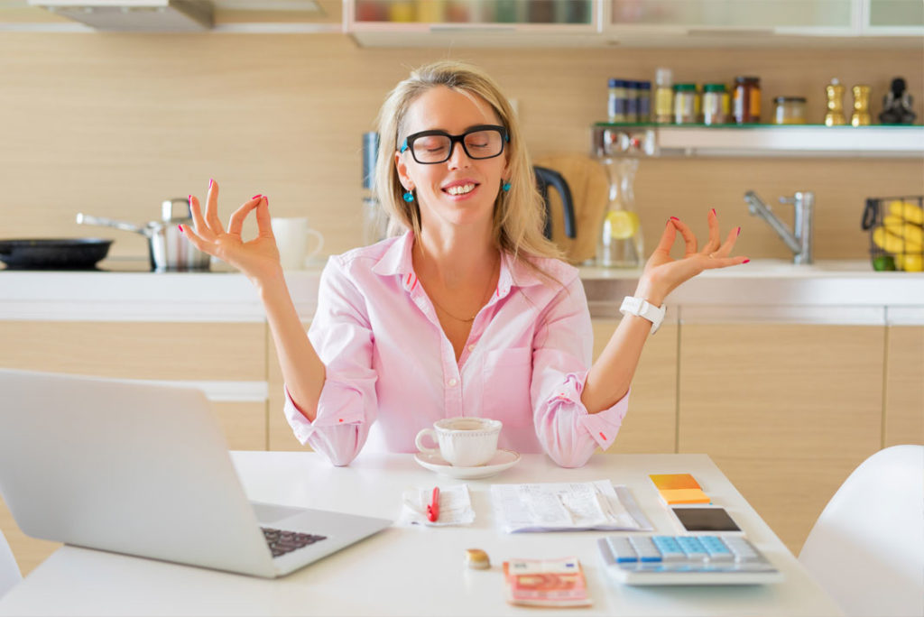 Financially free and zen woman sitting at a kitchen table