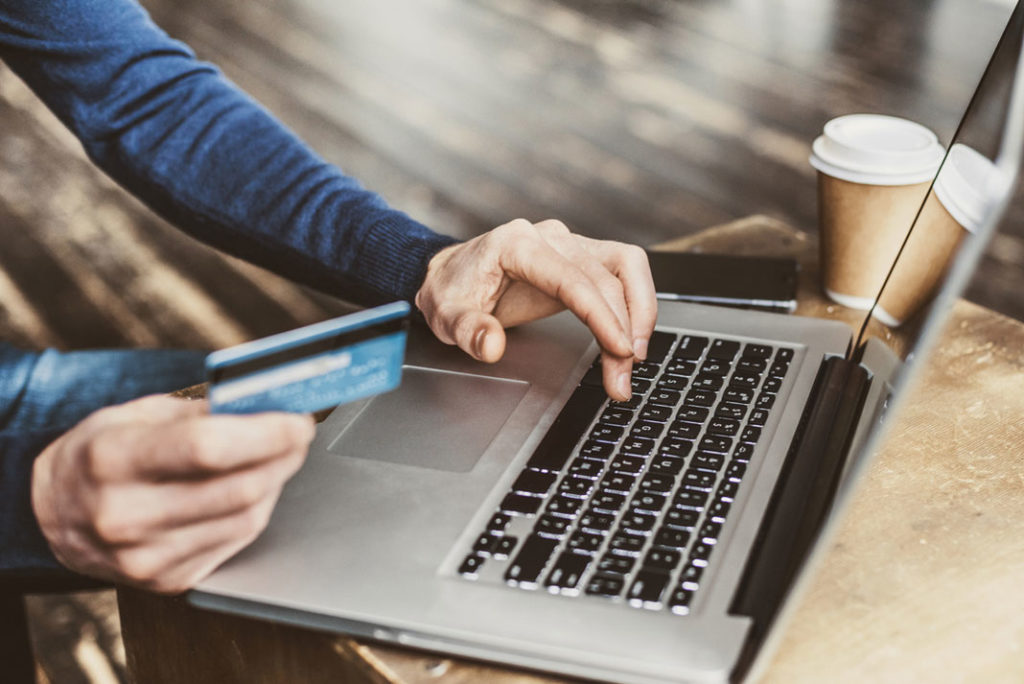 Man in blue jumper sat at laptop holding a credit card