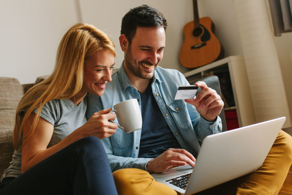 smiling couple in front of laptop holding a credit card online shopping
