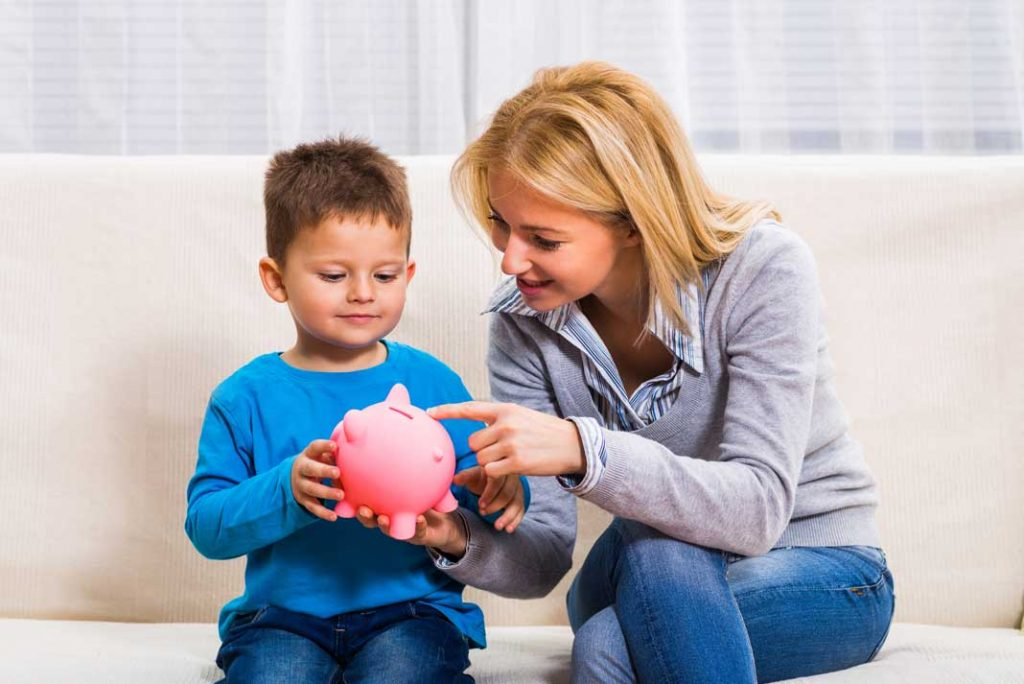 woman and son sat on sofa with pink piggy bank